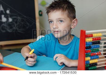 Thinking schoolboy working on a math project at home