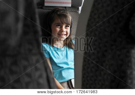 Plane passenger (child girl age 6-7 ). Child in in airplane cabin watching inflight movie / listening to music on headphones. Air travel concept. Real people copy space