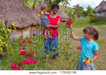 Tourist girls (age 3 and 6 ) interact with Indigenous Fijian woman and pick up flowers during a visit in Navala village on the highlands of Viti leavu island Fiji. Real people