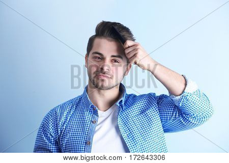 Handsome young man combing hair on color background