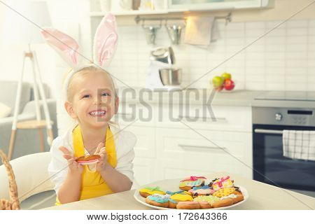 Cute little girl with Easter cookies at kitchen