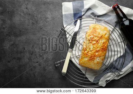 Metal stand with tasty loaf of beer bread on table