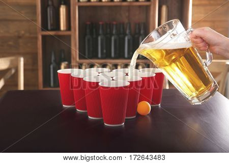 Beer pouring in plastic cups on table. Beer pong concept
