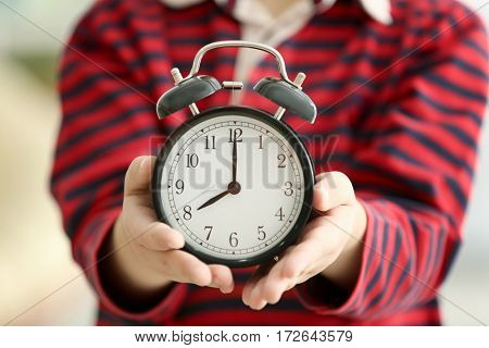 Cute little boy with alarm clock, closeup