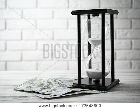 Dollar banknotes and sandglass on brick wall background