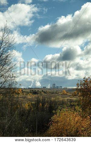 Smokestacks Of Factory At Distance With Cloudy Sky At Autumn