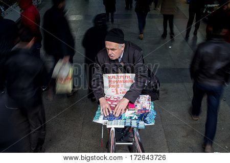 ISTANBUL TURKEY - DECEMBER 29 2015: Blind seller organizing his merchandise while pedestrians are passing around with speed blur effects Picture of a blind merchant at the bottom of stairs surrounded by people passing at a high speed