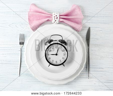 Alarm clock in empty plate on wooden background