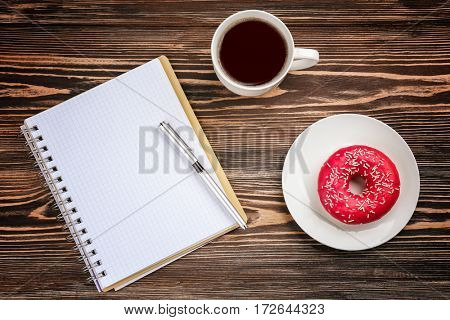 Tasty donut with cup of coffee and notebook on wooden table