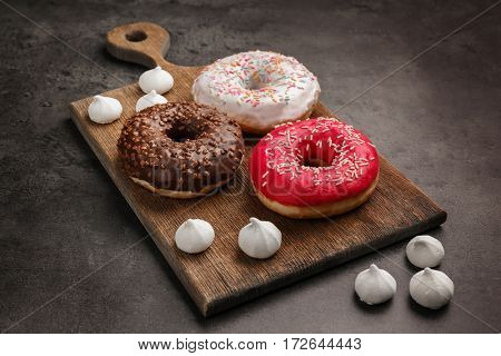 Tasty donuts on cutting board