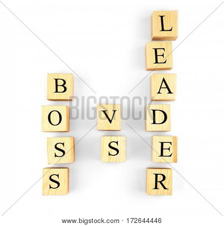 Towers of wooden cubes with text BOSS VS LEADER isolated on white