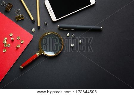 Flat lay of stationery and smart phone on black background