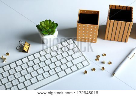 Workplace with keyboard and golden stationery