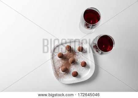 Chocolate truffles and glasses with red wine on white background