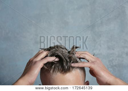 Young handsome man washing hair on gray background