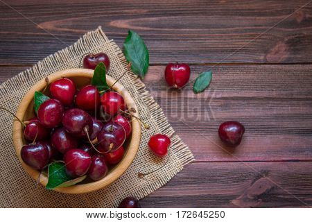 Cherries With Leaves In A Wooden Plate On The Sacking