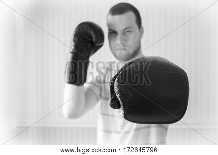 horizontal black and white  close up image of a young caucasian adult male wearing boxing gloves in a fighting stance and throwing a punch towards camera.