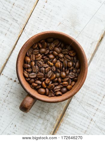Whole coffee beans in the brown cup which stands on a wooden floor. White floor.