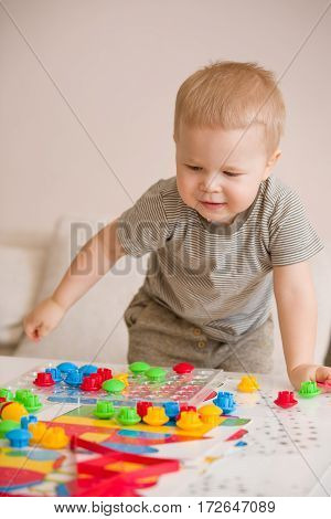 Cute preschooler child boy plays with mosaic at home. A blond little toddler playing in kid's room. Leisure activities. indoors. Boy sorting colorful children's plastic mosaic. Development.3
