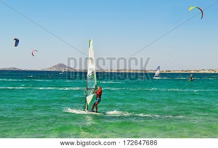 NAXOS GREECE, AUGUST 27 2014: people doing kitesurf and windsurf at Naxos island Cyclades Greece. Editorial use.