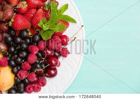 Assortment of juicy fruits on white plate and turquoise table background. Banana strawberries blueberries raspberries gooseberry blackcurrant decorated with mint for summer dessert or snack.