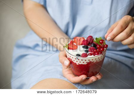 Woman holding smoothie bawl with organic yogurt berries and mint. Homemade yogurt in girl's hands served with raspberry strawberry and blueberry. Breakfast. snack. Healthy eating lifestyle concept