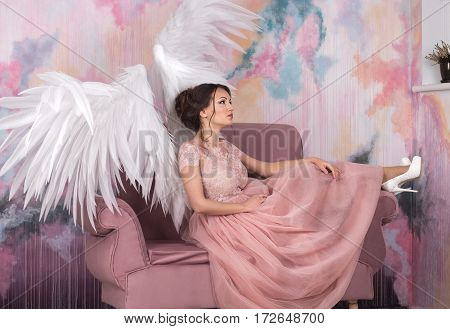 beautiful young model with open angel wings sitting on sofain the studio. white background