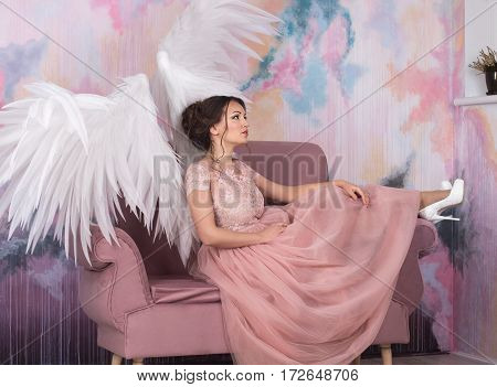 beautiful model with open angel wings sitting on the sofa with pink sky background