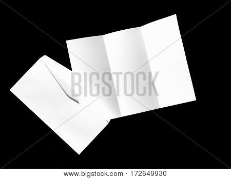 blank of letter paper and white envelope isolated on black background
