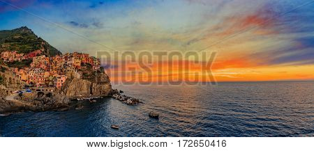 Colorful traditional houses on a rock over Mediterranean sea on sunset, Manarola, Cinque Terre, Italy
