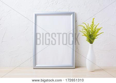 Silver frame mockup with ornamental grass in exquisite vase. Empty frame mock up for presentation artwork.