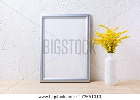 Silver frame mockup with ornamental yellow flowering grass in vase. Empty frame mock up for presentation artwork.