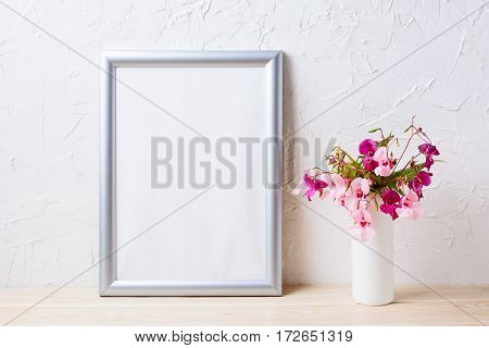 Silver frame mockup with pink and purple flower bouquet. Empty frame mock up for presentation artwork.
