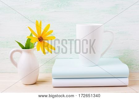 White cappuccino mug mockup with yellow rosinweed flowers in pitcher. Empty mug mock up for brand promotion.
