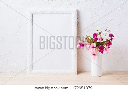 White frame mockup with pink and purple flower bouquet. Empty frame mock up for presentation design.