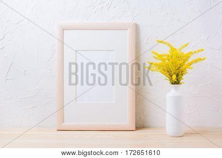 Wooden frame mockup with ornamental yellow flowering grass in vase. Empty frame mock up for presentation design.