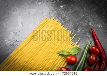 Uncooked Spaghetti With Tomatoes, Pepper And Basil On A Gray Bac
