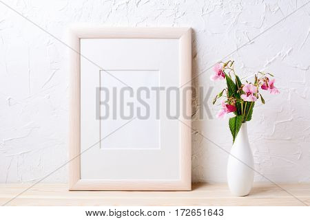 Wooden frame mockup with purple wildflowers in elegant vase. Empty frame mock up for presentation design.