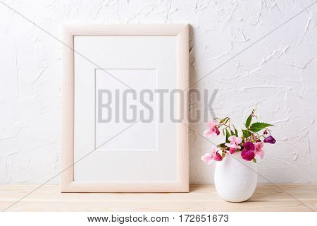 Wooden frame mockup with purple wildflowers in flowerpot. Empty frame mock up for presentation design.