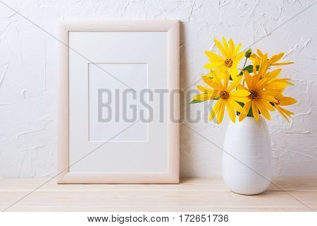 Wooden white frame mockup with yellow rosinweed flowers in pitcher. Empty frame mock up for presentation artwork.
