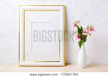 Gold decorated frame mockup with flower bouquet in elegant vase. Empty frame mock up for presentation artwork.