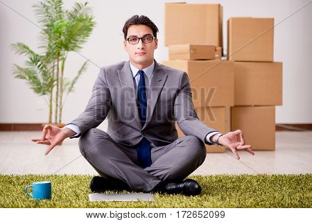 Businessman meditating on the office floor