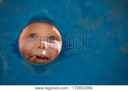 Closeup portrait of cute little toddler boy looking into blue wooden frame at playground. Curiosity exploration and leaning. Activities for children outdoors. Preschool daycare. Small boy playing