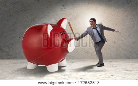 Angry man with baseball bat hitting piggybank