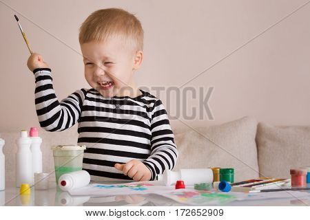 Portrait of smiling cute toddler boy drawing at home with colorful paints and brush. Creative child having fun. Educational concept