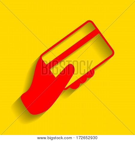 Hand holding a credit card. Vector. Red icon with soft shadow on golden background.