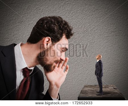 Businessman speaks whispering to a small man. Business suggestion  concept