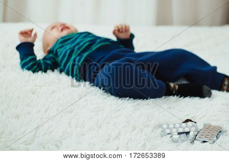 the child is lying next to the pills and crying