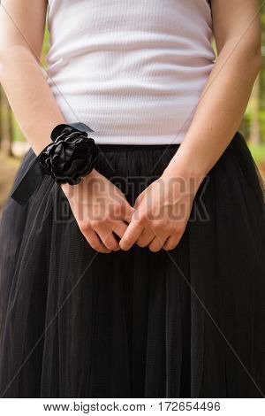 A young girl in a white tank top and black fluffy skirt in the forest outdoors. black flower wristband. Celebration, party. Bridesmaid. Wedding.