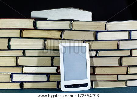 E-book On Background Of Big Pile Of Books On Dark Background Close Up